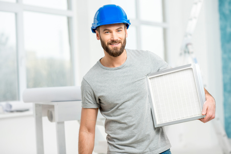 Worker with air filter Stock Photo