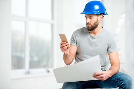 Handsome repairman or builder in helmet working with drawings and phone on the renovation of apartment interior