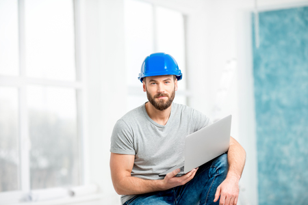 Portrait of a handsome builder, foreman or repairman in the helmet sitting with laptop in the white interior