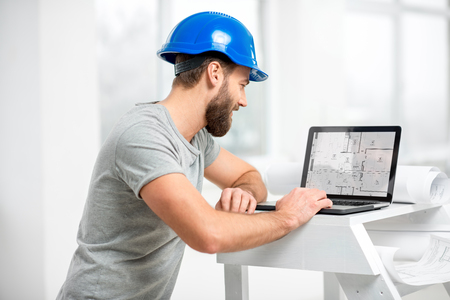 Architect working with laptop at the structure interior