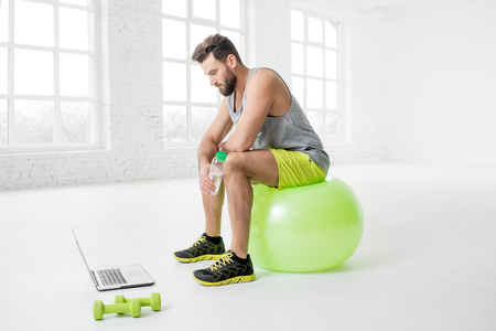 fitball: Man with laptop in the gym