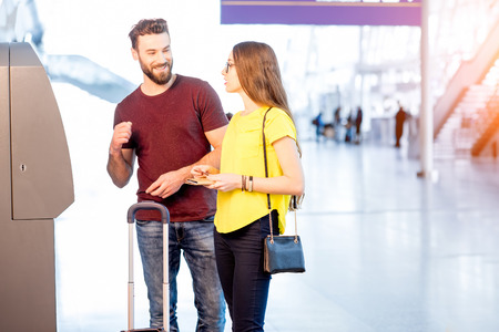 withdrawal: Couple withdrawing money at the airport Stock Photo