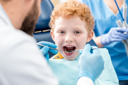 Dentist examinating boys teeth Stock Photo