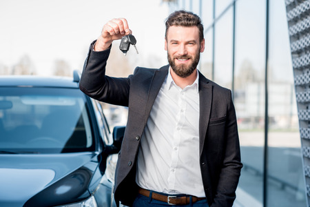 차 근처에 열쇠가있는 남자
