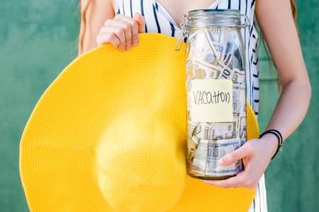 Woman holding a jar full of money for summer vacation
