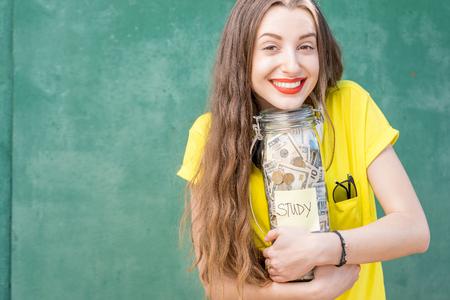 Femme tenant une bouteille pleine d'économies d'argent pour étude