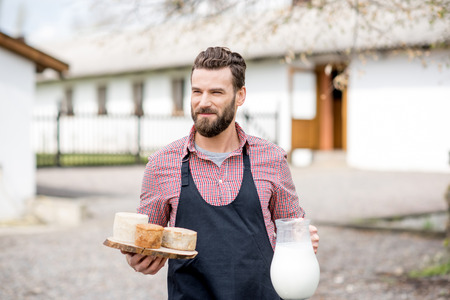 Farmer with milk and cheese outdoors
