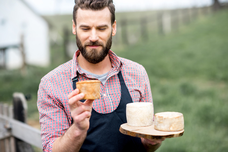 Farmer with cheese outdoors