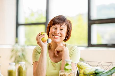 Oudere vrouw met gezond voedsel binnen Stockfoto