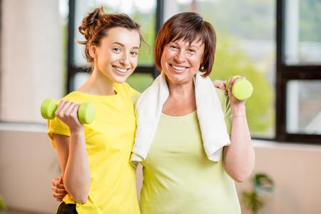 若者と年配の女性が室内で運動