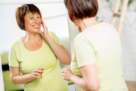 Mujer mayor mirando hacia el espejo Foto de archivo - 77651029