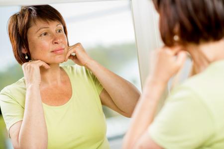bathroom mirror: Older woman looking into the mirror