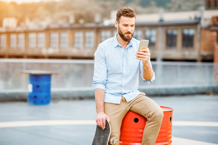 Hipster with smartphone on the rooftop