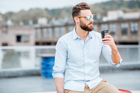 Businessman having a coffeebreak on the rooftop Stock Photo