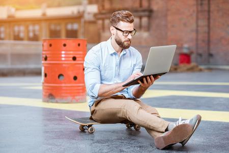 Hipster die met laptop op het dak werkt