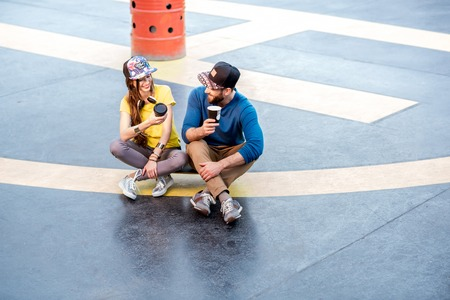 Stylish couple in caps sitting together with coffee cups on the skateboard outdoors on the helipad ground