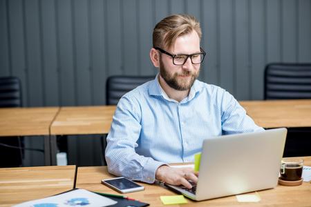 Hombre que trabaja con el ordenador portátil dentro Foto de archivo - 78052016