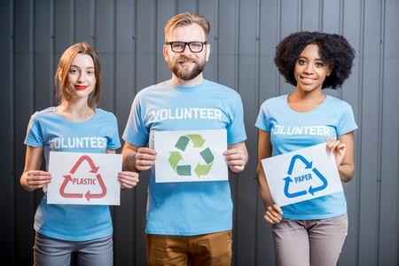 Les bénévoles ayant des signes de tri des déchets Banque d'images - 78052036