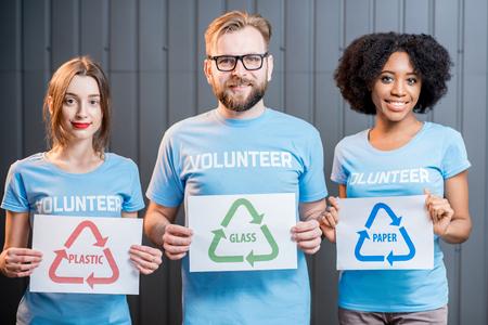 Les bénévoles ayant des signes de tri des déchets Banque d'images - 78052039