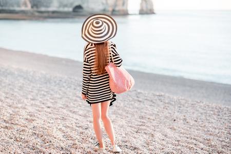 outerwear: Woman enjoying rocky beach Stock Photo