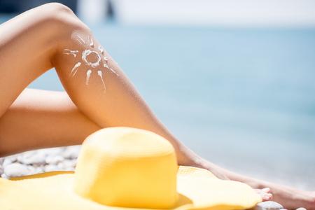 Woman sunbathing with sunscreen lotion