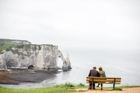 岩の多い海岸線の景色を楽しみながら高齢者のカップル