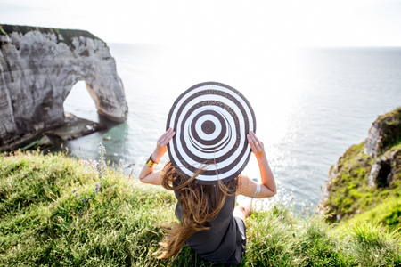 normandy: Young woman in striped hat enjoying great view on the famous rocky coastline near Etretat town in France