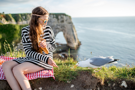 Woman having a picnic on the rocky coastline Stock Photo