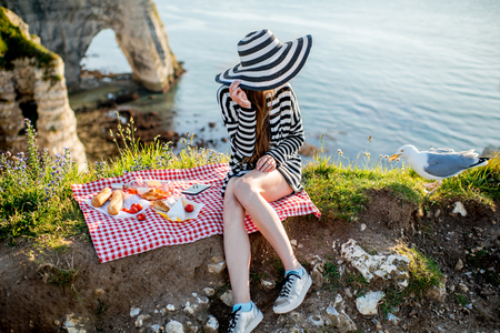 Femme ayant un pique-nique sur le littoral rocheux Banque d'images - 80272131