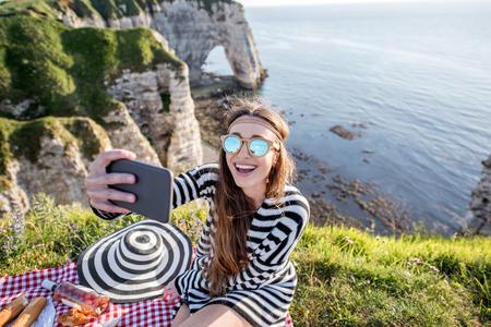 Woman having a picnic on the rocky coastline Stok Fotoğraf