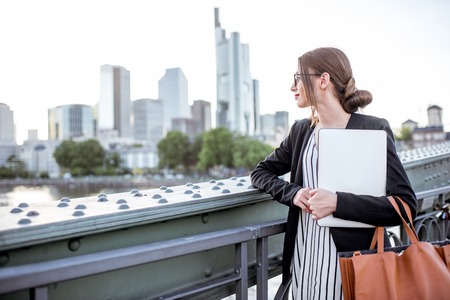 屋外でノート パソコンを持つ実業家