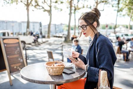 Mujer sentada en el café al aire libre Foto de archivo - 81370150