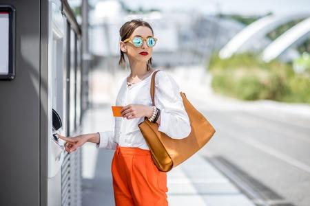 Vrouw die een kaartje koopt of buiten ATM gebruikt Stockfoto