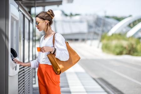 Femme achetant un billet ou en utilisant ATM à l'extérieur Banque d'images - 81474218