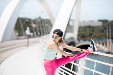 Woman in sportswear outdoors on the modern bridge