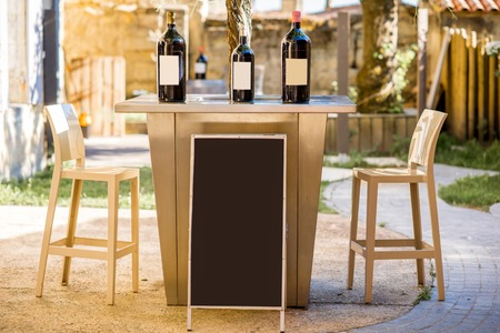 Wine bottles with blank label and board to copy paste outdoors on the tabel