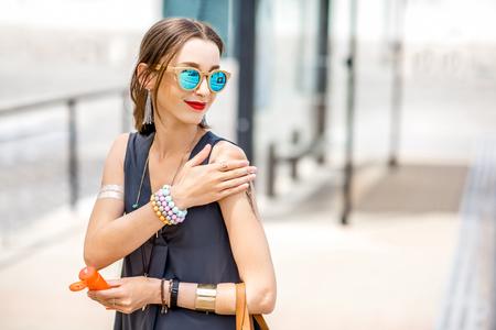 Woman applying sunscreen lotion