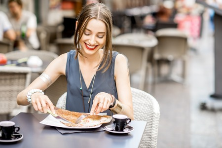 Woman eating galette meal at the restaurant in France