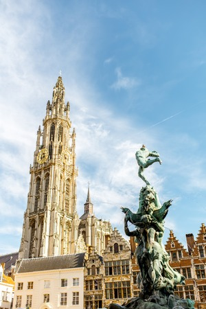 View on the beautiful buildings with fountain sculpture and church tower in the center of Antwerpen city in Belgium