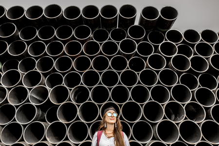 Young woman on the stack of iron tubes background