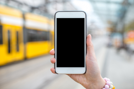 Holding a smart phone on the tram stop background