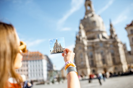 Woman holding a card with photo of Our Lady church in Dresden city, Germany