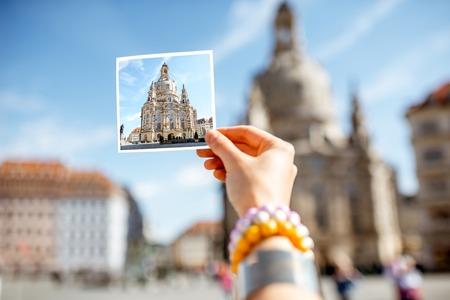 Frau, die eine Karte mit Foto unserer Damenkirche in Dresden-Stadt, Deutschland hält Standard-Bild - 82718126
