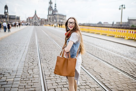 Lifestyle portrait of a business woman walking the bridge in the old town of Dresden, Germany