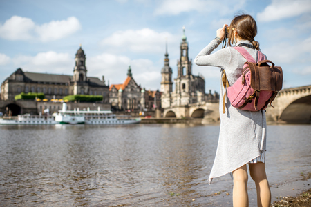 Young woman tourist photographing beautiful view on the riverside of the old town of Dresden, Germany Stock Photo