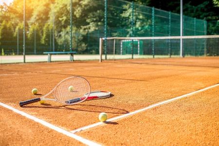 cour de tennis orange avec raquettes et boules à l & # 39 ; extérieur