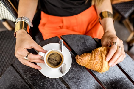 Holding coffee and croiisant