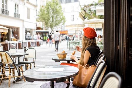 カフェでフランスの朝食を持っている女性