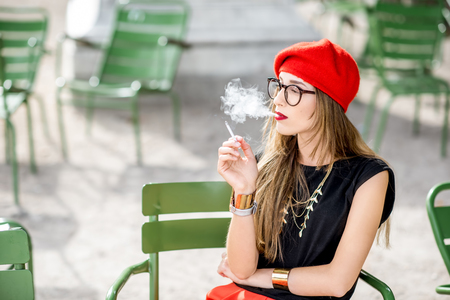 Woman smoking outdoors Imagens