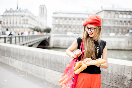 Woman walking with french food in Paris